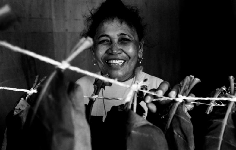 Tabac - Outre les cultures vivrières, les Wallisiens et Futuniens plantent aussi du tabac qu'ils font sécher et préparent avant de le fumer. Ici, Thérèse pose devant les plants de tabac qui sèchent dans une pièce de sa maison, au squat de Sakamoto.