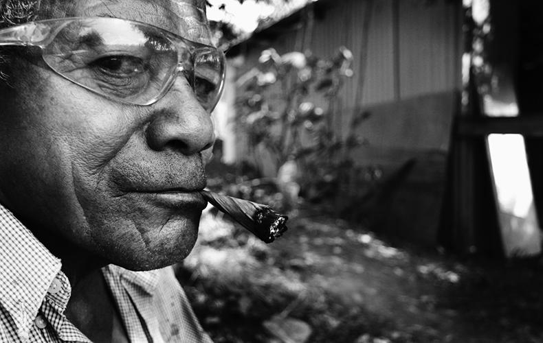 Faire une pause - Près du champ que cultive le groupe d'amis, Jean Soane prend une pause en fumant du tabac wallisien.