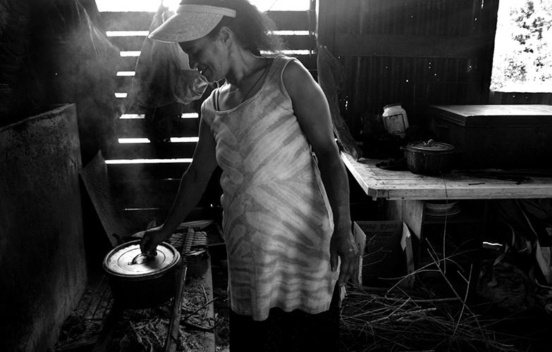 """Hospitalité - Originaire de Houailou, Evelyne vit au squat de Yelos depuis 1997. En saison fraîche, elle plante du manioc, des patates. Elle était méfiante la première fois qu'elle m'a vue avec l'appareil. """"D'abord, t'es qui toi?"""" Et puis là finalement, c'est café, crêpes de bananes et causerie. On se pose avec ses filles, Mélissandre, 12 ans, et Aurore, 1 ans. Francisca, la jumelle de Mélissandre, se cache. On lui a coupé les cheveux ce matin et elle boude."""