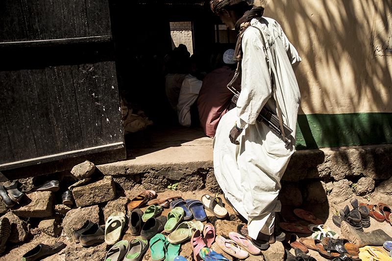 """Plusieurs hommes entrent dans la mosquée pour la prière du vendredi en laissant leurs chaussures dehors mais pas leur kalashnikov. Selon Ismaïl Nafi, imam de Bossangoa, """" il y a beaucoup de souffrance des deux côtés. Beaucoup de gens sont morts. Et pas des militaires, mais des civils. Un grand nombre de Musulmans ont été tués à Bossangoa et dans ses environs."""""""