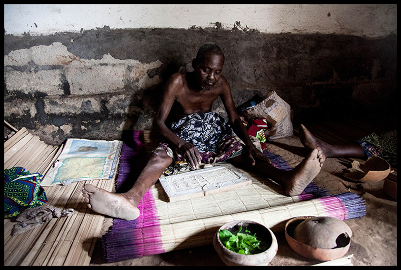 Bokhônon Dah Hessou jette des colas puis trace dans la poudre de kaolin des traits parallèles, selon la position des noix quand elles retombent. Il consulte le Fâ.  Le Fâ – aussi appelé Ifa- est un système de géomancie divinatoire africaine ajouté en 2005 par l'UNESCO à la liste du patrimoine oral immatériel de l'humanité.