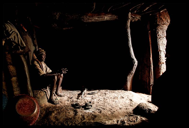 """Diene Ndah, à l'intérieur de son Tata. Tous ses enfants sont scarifiés. Sa femme, Kanti Kouabo, porte une croix autour du cou et allie  - comme de nombreux Béninois - culte animiste et religion catholique. """"Quand on va à l'église, dans toute prière, on parle de Dieu. Et sur les fétiches, quand on demande quelque chose on parle aussi de Dieu. Tout est lié""""."""