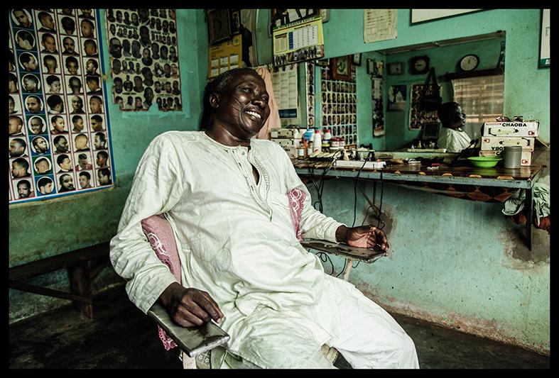 """Moustapha Ganiou, dans son salon de coiffure de Natitingou. """"Ce que j'ai sur les joues là, ça montre mon ethnie, que je suis Yoruba. Et je suis fier d'être Yoruba. Je suis à l'aise avec ça dans ma peau! Mes enfants? Non, ils ne portent pas ça. Je n'ai pas choisi cela pour eux, parce qu'aujourd'hui, le monde a évolué."""""""