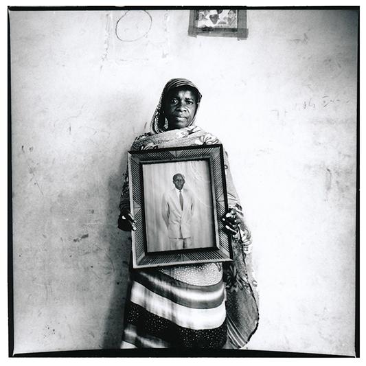 A Louga, Ndeye Ba fut l'une des seules épouses d'émigrés à m'autoriser à la photographier à visage découvert. Sans nouvelle de son homme depuis presque deux decennies, elle parait encore abasourdie par cette attente qu'elle refuse de transformer en deuil. Elle n'est ni divorcée, ni veuve. Elle n'a jamais pu se remarier. Elle montre un portrait de son mari, en Belgique la dernière fois qu'elle l'a eu au téléphone, il y a plus de 15 ans. Elle est toujours à sa recherche :