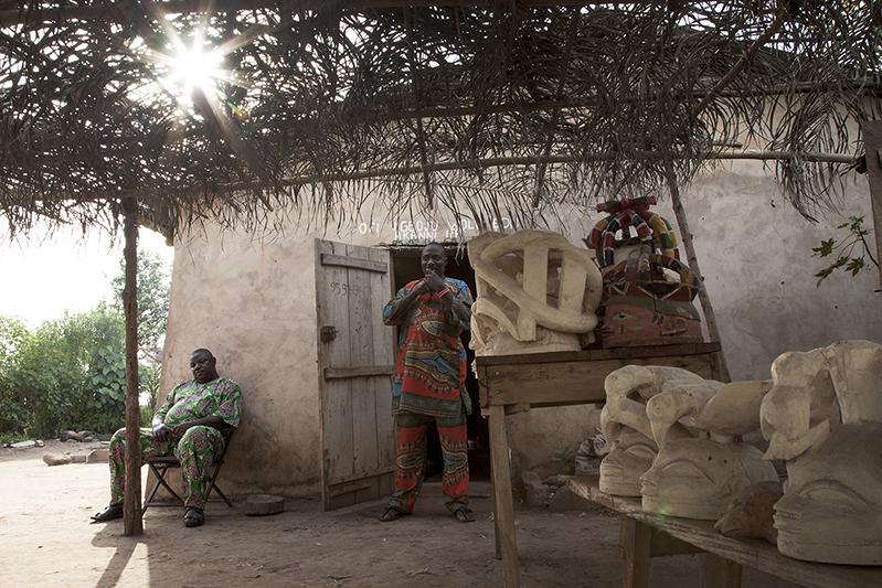 Bernardin Adebayo sculpte des masques Guèlèdè depuis plus de trois décennies. Sur ses masques, des paraboles animalières ou des symboles de pourvoir. Le sculpteur est aussi danseur de Guèlèdè, et manie l''akpala', ce pipeau qui marque le début des danses nocturnes. Ofia, Bénin, 2017. ©Laeïla Adjovi