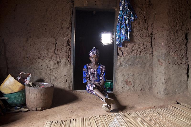 Adjima Sande, agée de 12 ans, a déjà joué le rôle d''Arugba' à cinq reprises. Lors de la danse Guèlèdè, 'Arugba', qui signifie 'porteuse de calebasse' en Yoruba, est une jeune vierge désignée dans la famille des danseurs. Elle arrive en éclaireur juste avant la sortie d'Efe, le masque le plus important. La calebasse fermée qu'elle porte sur la tête symbolise la puissance d'Awon Iya. Ofia, Bénin, 2017. ©Laeïla Adjovi