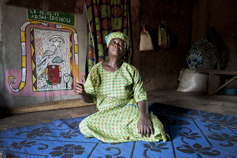Marguerite Adjahi s'occupe de ses frères et beaux frères quand ils dansent en coulisse, jouant ainsi de manière informelle le rôle de 'Iyaidjo'. Elle affirme que ses ancêtres font partie de ceux qui ont amené la danse Guèlèdè d'Ilobi au Nigéria jusqu'à Ofia. Ofia, Bénin, 2017. ©Laeïla Adjovi