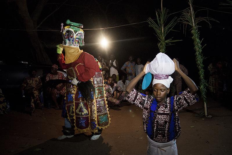 La jeune porteuse de calebasse dansera aux côtés d'Oro Efe, sans sourire. Elle symbolise la présence des mères, qui veillent. Ofia, Bénin, 2017. ©Laeïla Adjovi