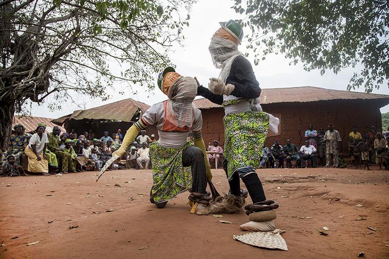Des danseurs Guèlèdè portant des masques masculins poursuivent la danse